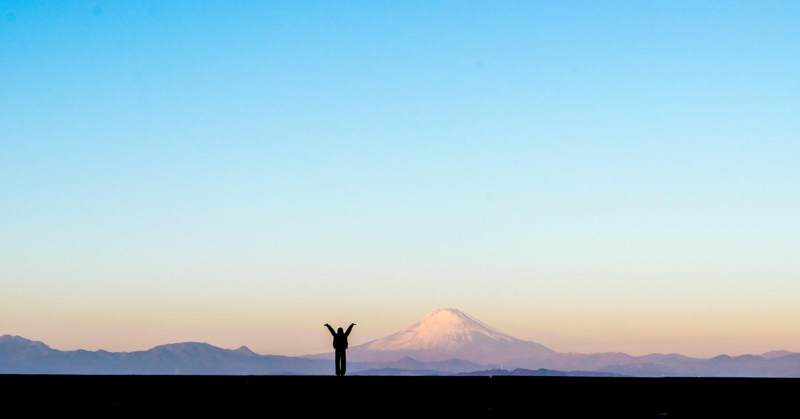「新年!富士山をバックに両手をあげる女性のシルエット」の写真