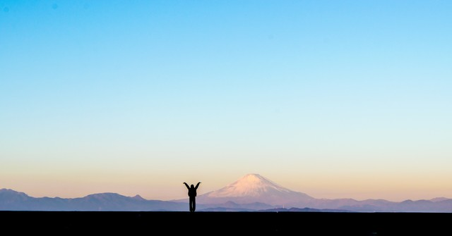 新年!富士山をバックに両手をあげる女性のシルエットの写真