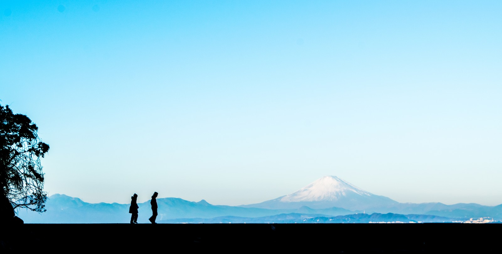 「富士山をバックに散歩する二人の男女(シルエット)」の写真