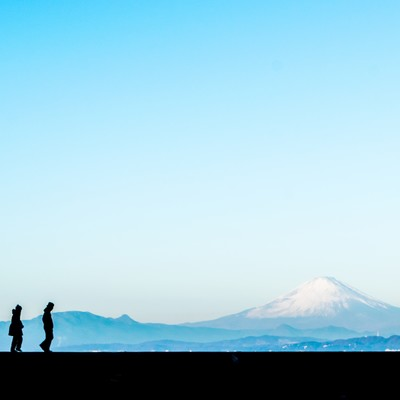富士山をバックに散歩する二人の男女(シルエット)の写真