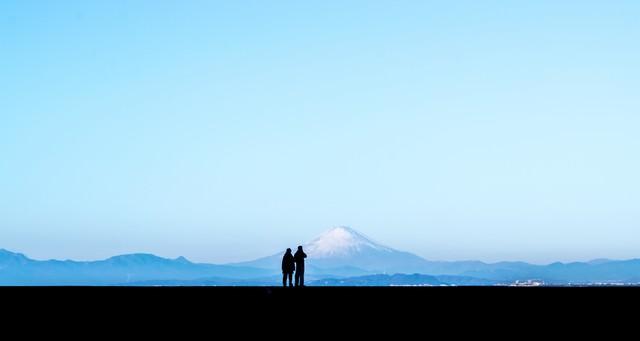 カップルで快晴の富士山を見ているシルエットの写真