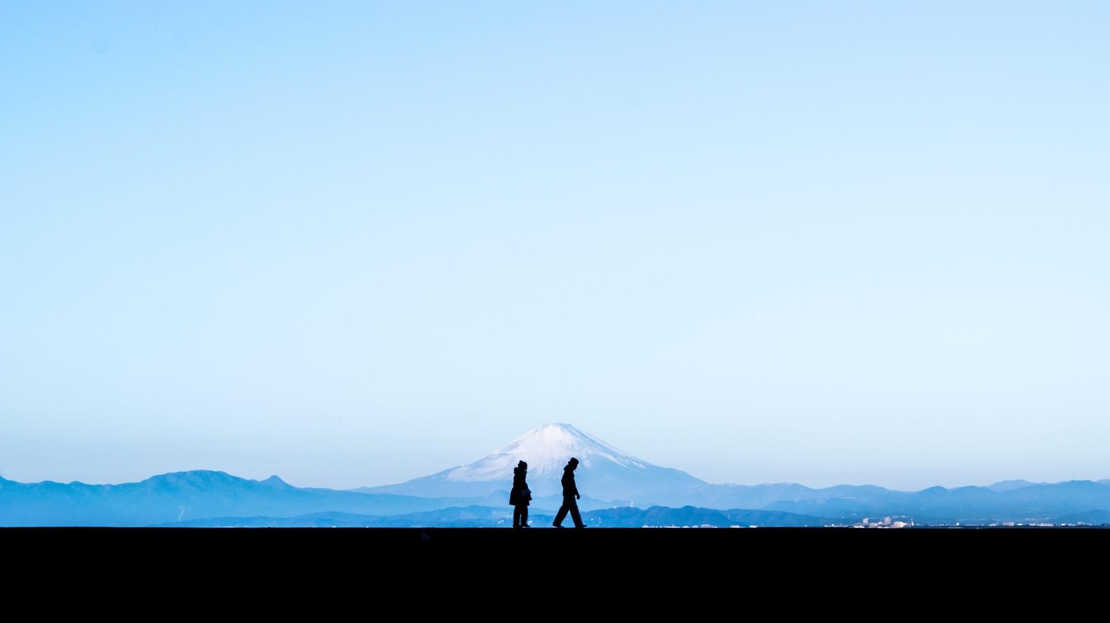 「富士山を見ながら散歩する恋人のシルエット」
