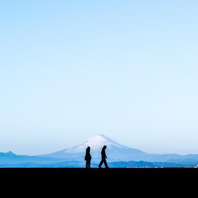 富士山を見ながら散歩する恋人のシルエットの写真
