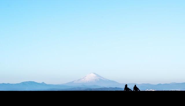富士山を見るカップルのシルエットの写真
