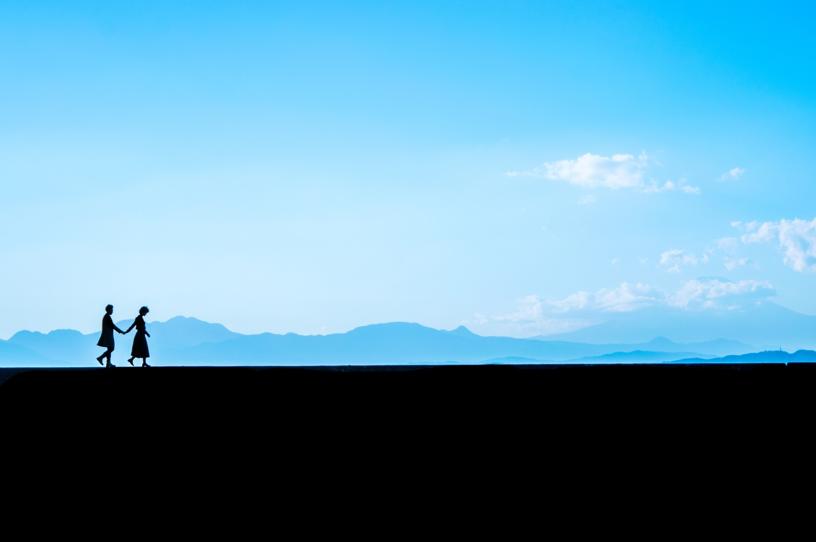 「うつむき歩く彼女と手を繋ぐ彼氏のシルエット」の写真