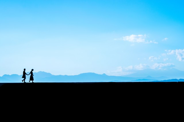 うつむき歩く彼女と手を繋ぐ彼氏のシルエットの写真