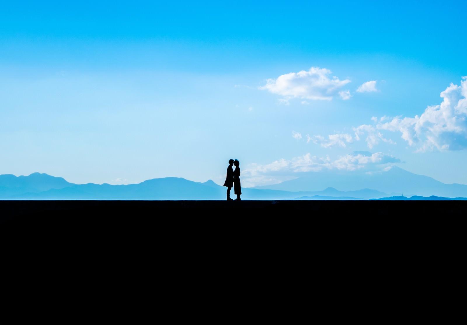 「景色のいい堤防の上で顔を近づける恋人」の写真