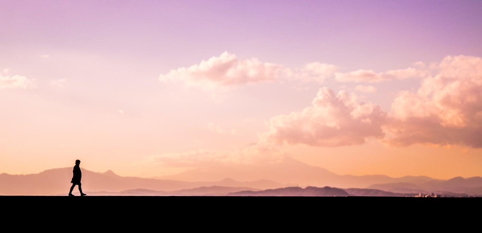 「夕焼け時刻に散歩する男性のシルエット」の写真