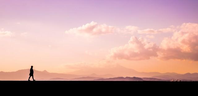 夕焼け時刻に散歩する男性のシルエットの写真
