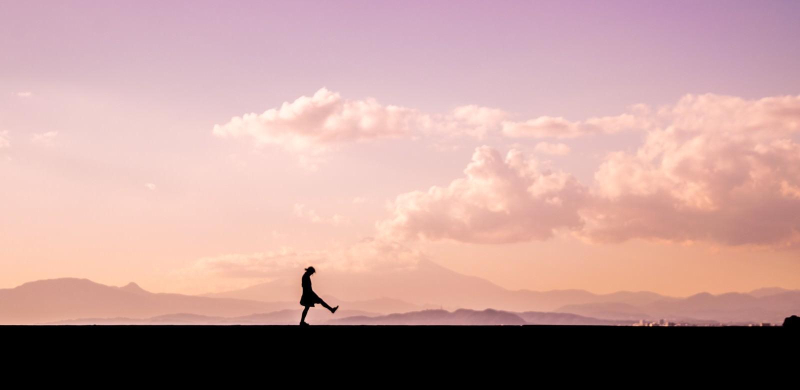 「足を高く上げて散歩する女性のシルエット」の写真