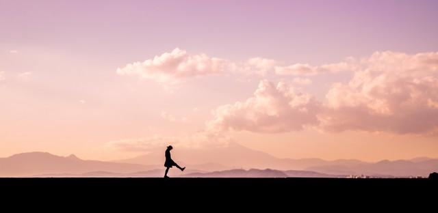 足を高く上げて散歩する女性のシルエットの写真