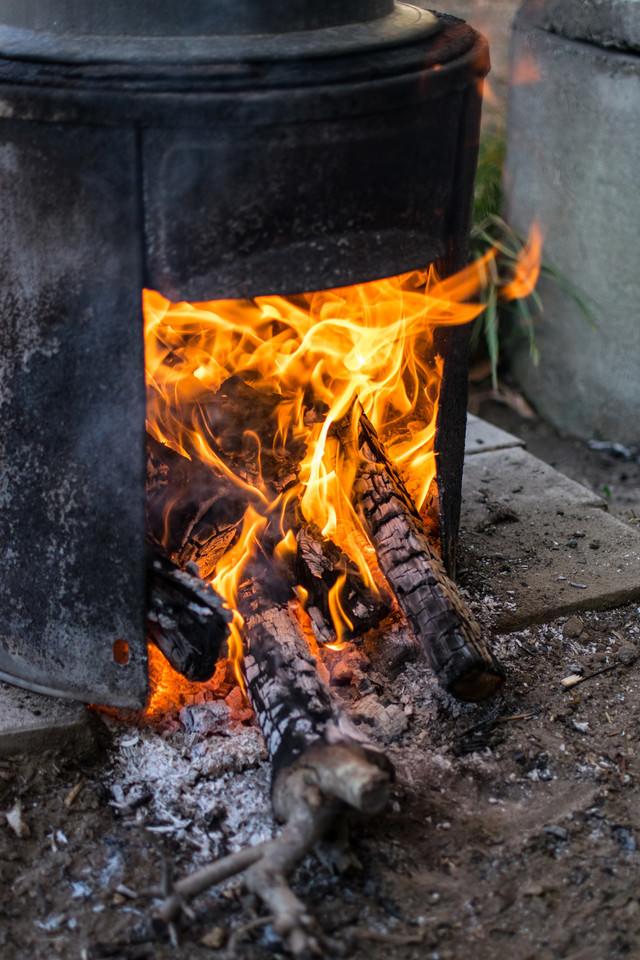 カマドに薪を入れるの写真