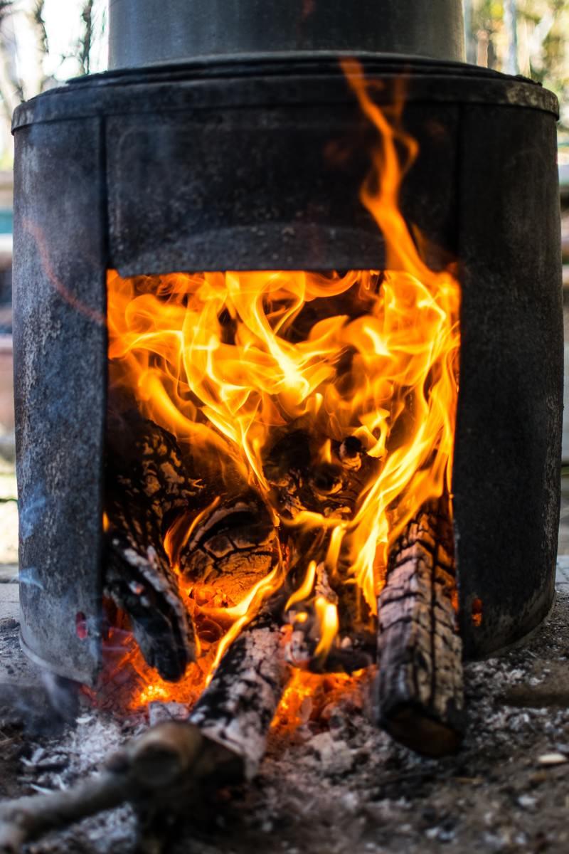 「釜戸で薪を燃やす」の写真