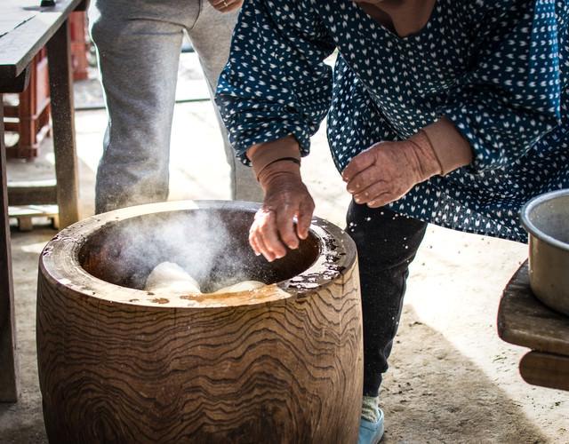 餅つきの様子(手水で餅をひっくり返す)の写真
