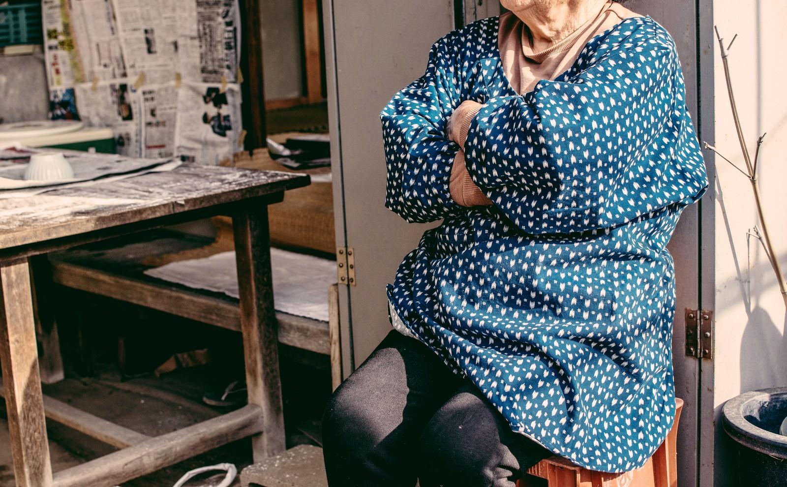 「椅子に腰掛け腕組みしながらひと休みする婆ちゃん | 写真の無料素材・フリー素材 - ぱくたそ」の写真