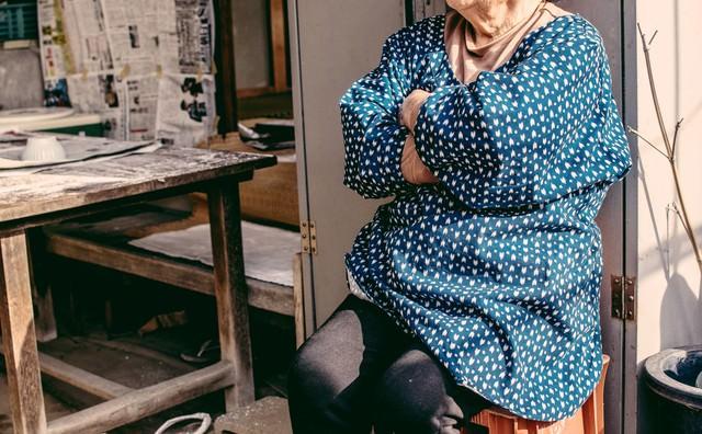 椅子に腰掛け腕組みしながらひと休みする婆ちゃんの写真