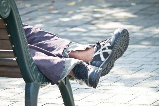 ベンチで寝る浮浪者の足の写真