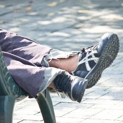 「ベンチで寝る浮浪者の足」の写真素材