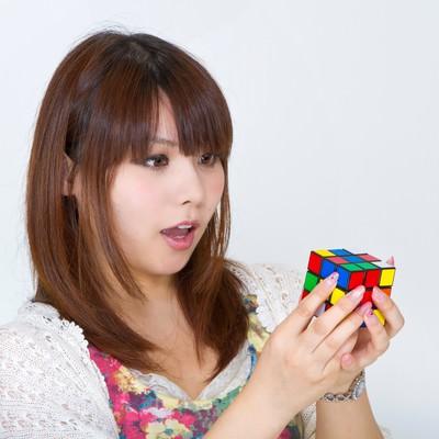 「ルービックキューブで驚いた表情の女性」の写真素材