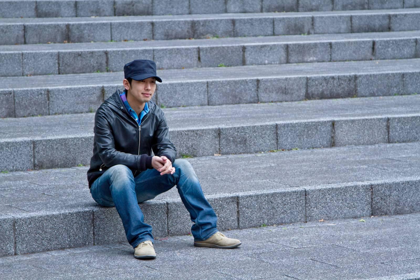 「階段に座り込む男性」の写真[モデル:大川竜弥]