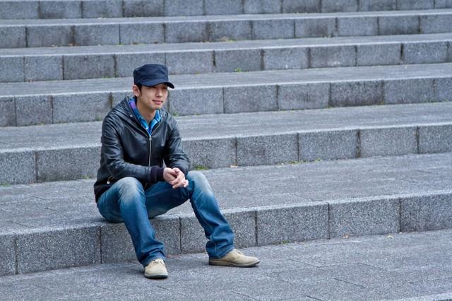 階段に座り込む男性の写真