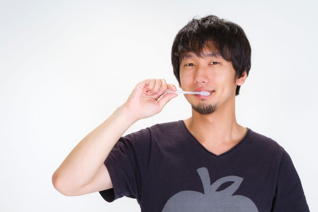 笑顔でハミガキをする男性の写真
