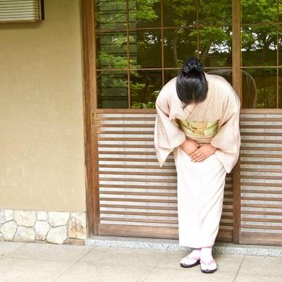 「玄関先でお出迎えする女将さん」の写真素材