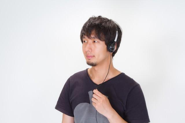 ヘッドフォンで音楽を聴く男性の写真