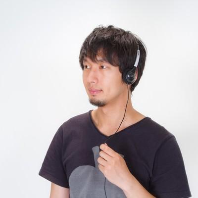 「ヘッドフォンで音楽を聴く男性」の写真素材