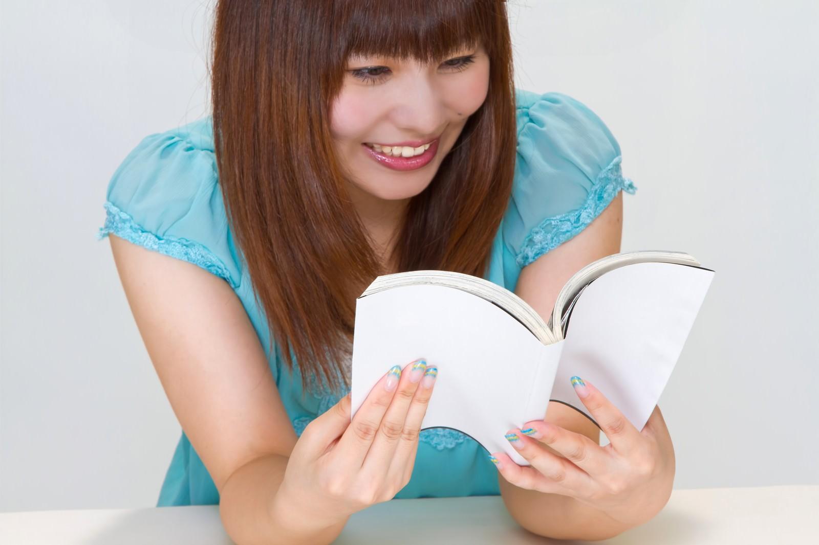 「本を読み笑う女性」の写真[モデル:Lala]
