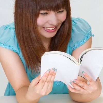 「本を読み笑う女性」の写真素材