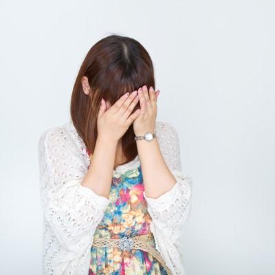 顔を覆い泣き出す女性の写真