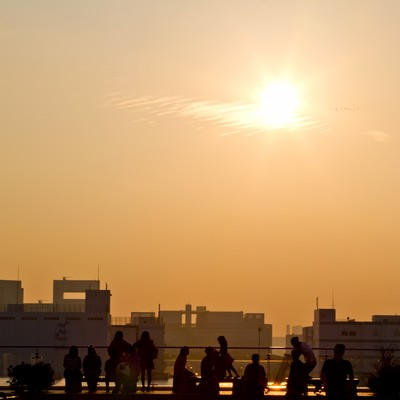 「夕焼けと人々のシルエット」の写真素材