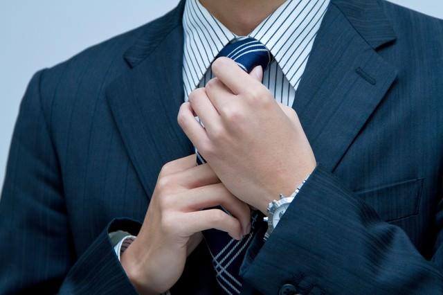 ネクタイを直すサラリーマンの写真