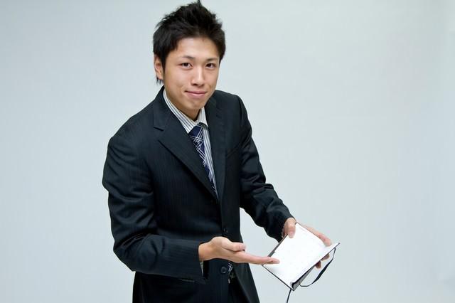スケジュール帳を見せるサラリーマンの写真