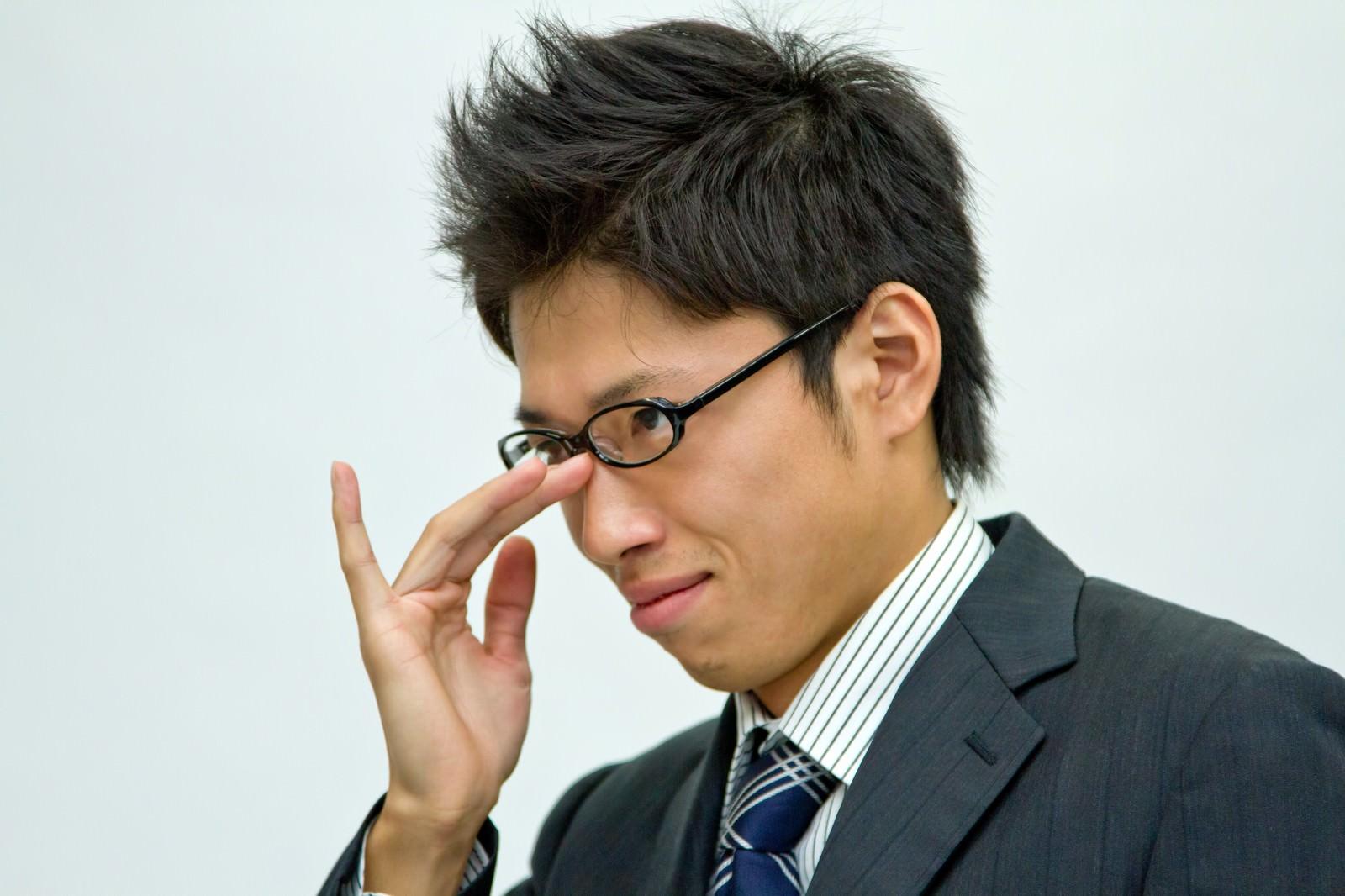 「悪巧みを考えるビジネスマン」の写真[モデル:恭平]