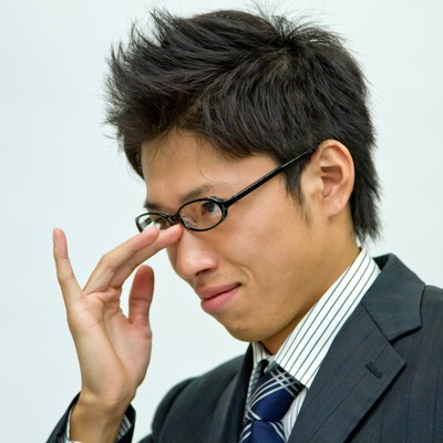 悪巧みを考えるビジネスマンの写真