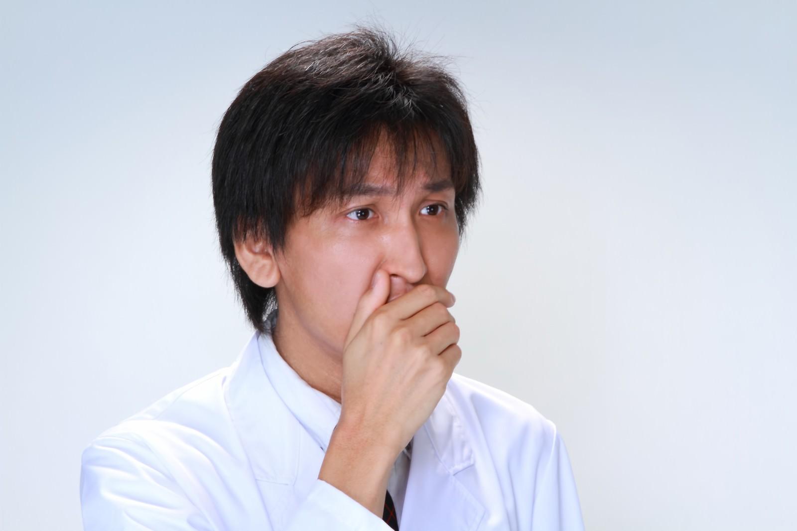 「口を覆う白衣の男性」の写真[モデル:ACE]