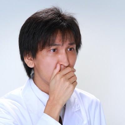 口を覆う白衣の男性の写真