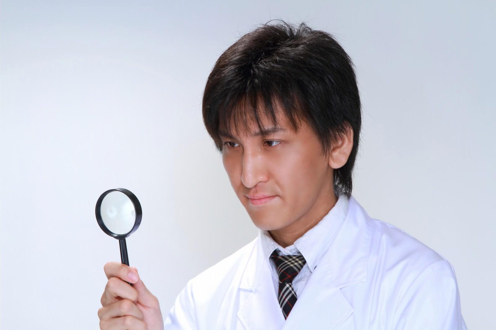 「虫眼鏡で確認する白衣の男性」の写真[モデル:ACE]