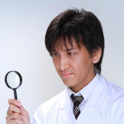 虫眼鏡で確認する白衣の男性の写真