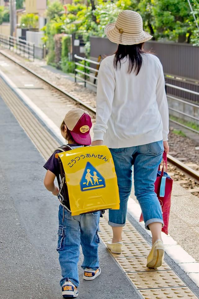 駅のホームを歩く親子の写真