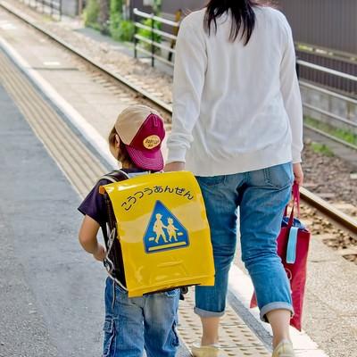 「駅のホームを歩く親子」の写真素材