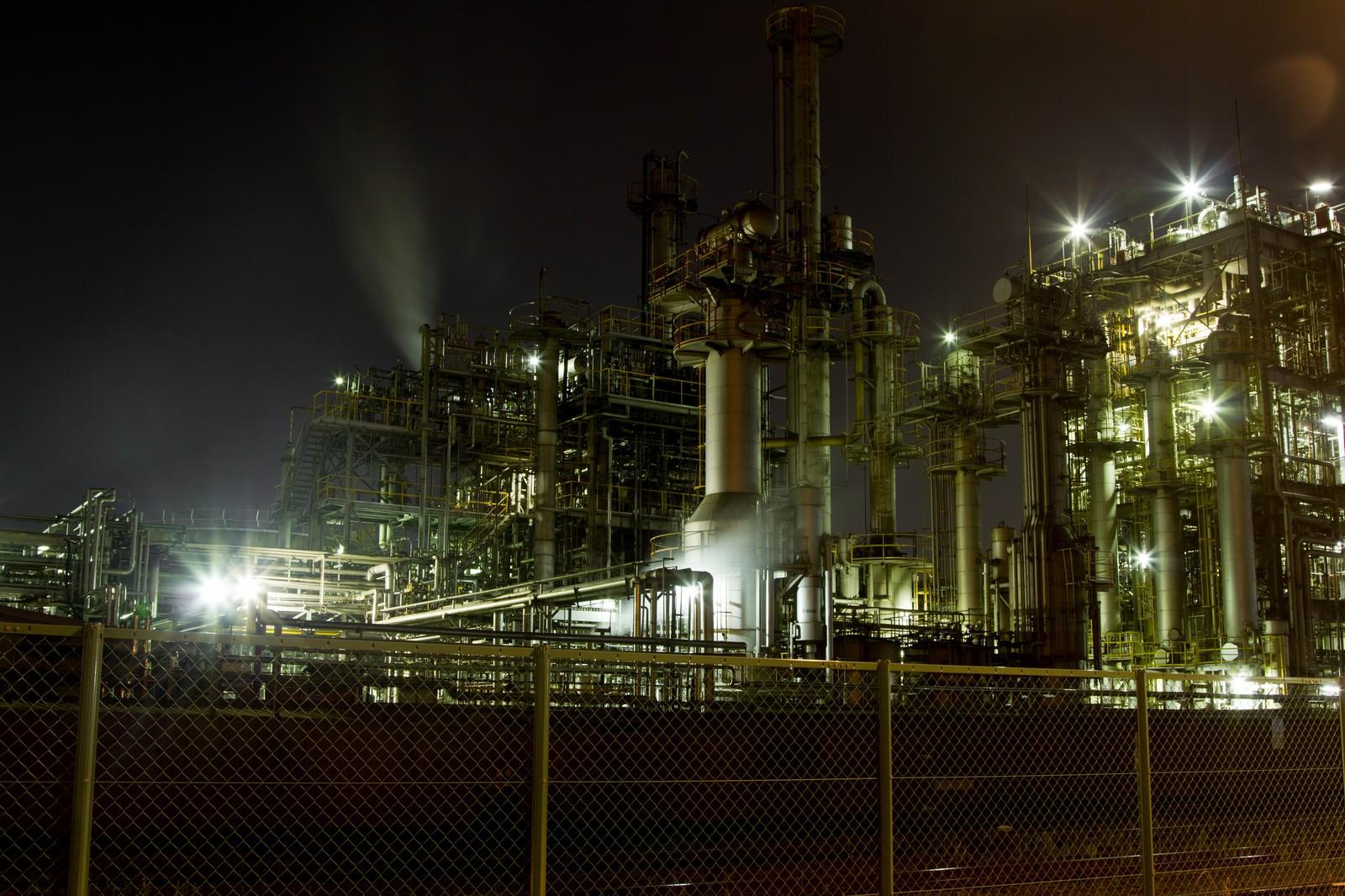 フェンスとライトアップされる工場のフリー素材