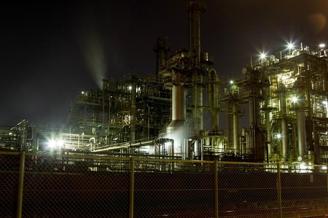 フェンスとライトアップされる工場の写真