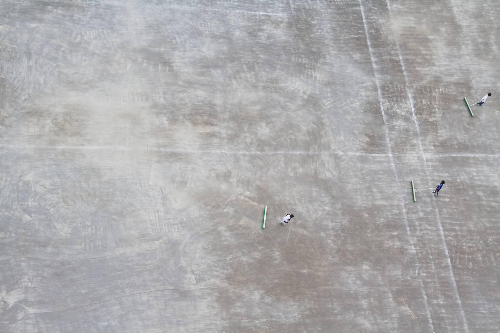 「運動場を整備する少年」の写真