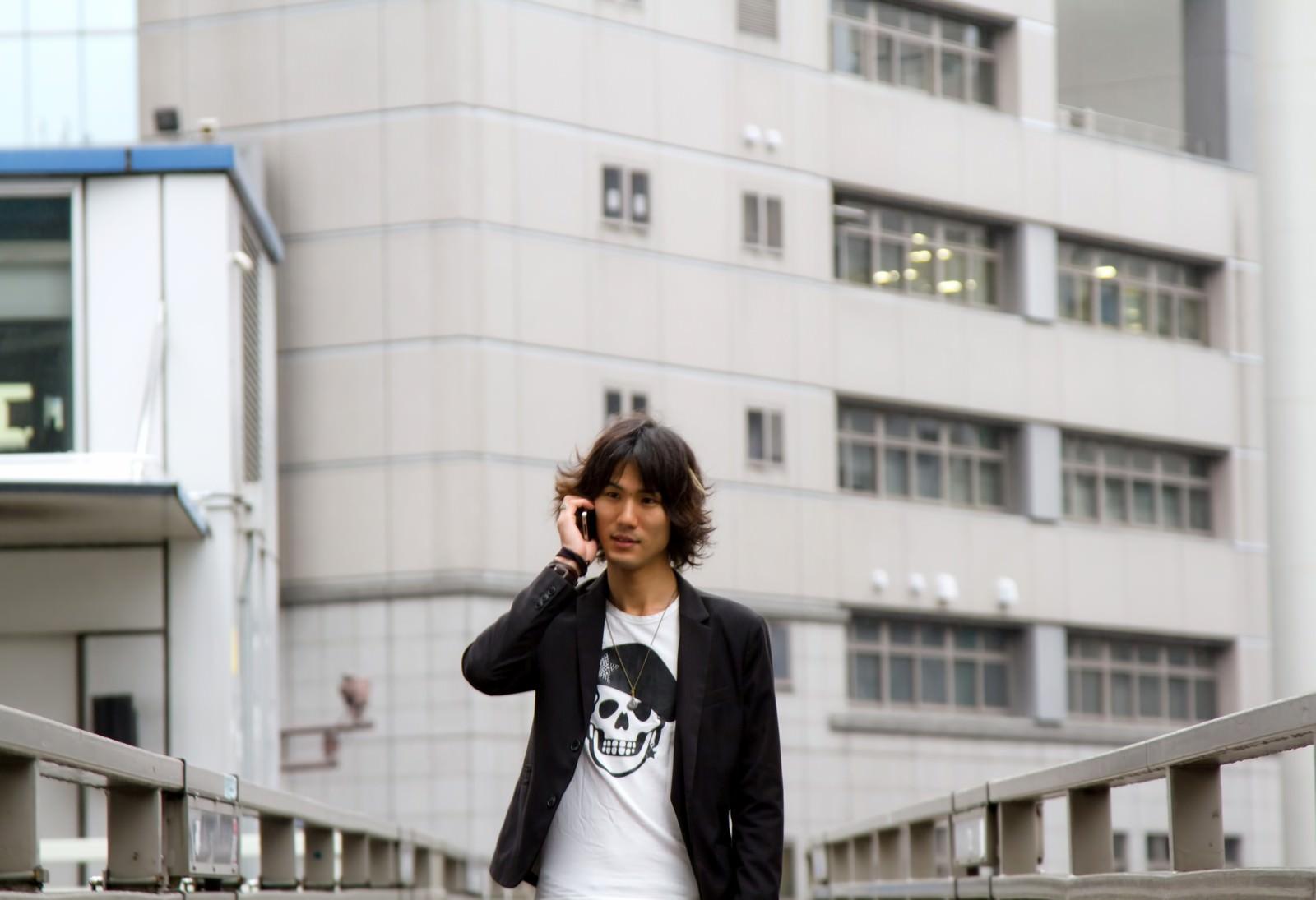 「歩道橋で電話する男性」の写真[モデル:村田裕章]