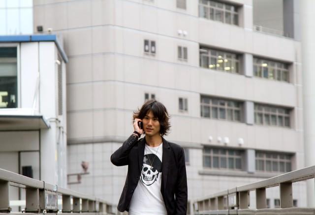 歩道橋で電話する男性の写真