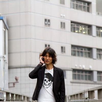 「歩道橋で電話する男性」の写真素材
