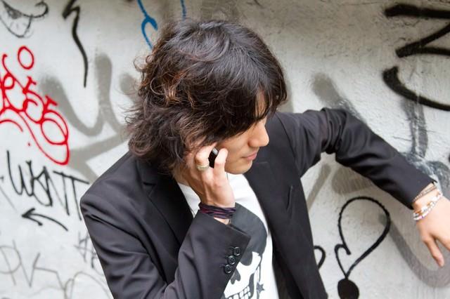 壁に手をかけ電話する男性の写真